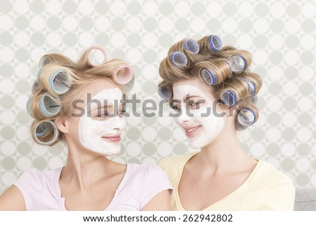 Young women with curlers and face mask - stock photo