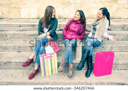 Young women with shopping bags sitting and smiling - Trendy multiracial girlfriends having fun on winter holidays - Asian woman with american girls talking outdoor - Concept of female fashion market - stock photo