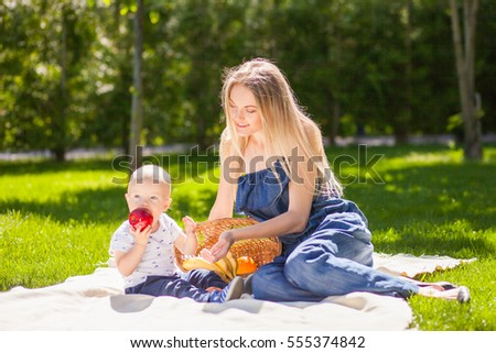 Young women with toddler boy in the park. Picknic