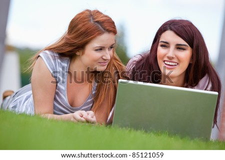 Young women working with a notebook while lying on the lawn