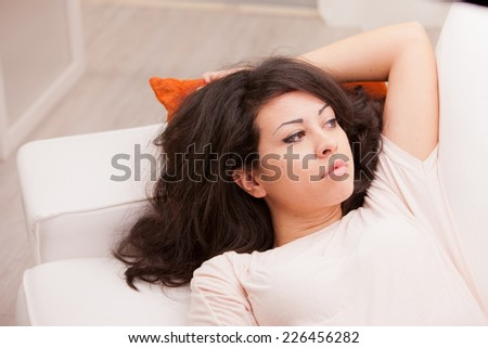 young wonderful woman relaxing on the sofa in her living room and thinking about her problems or the future or her love to come - stock photo