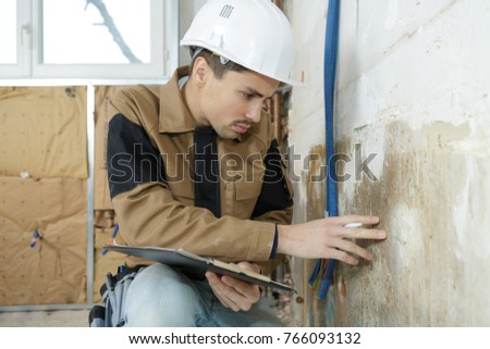 young worker checking the wall of a house