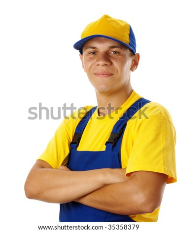 Young worker fold his arms, dressed in blue-and-yellow uniform and baseball hat, isolated over white - stock photo