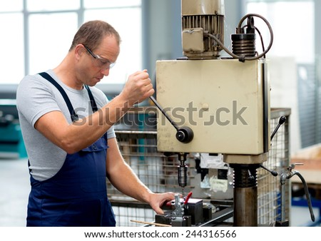 young worker in factory using drill machine - stock photo