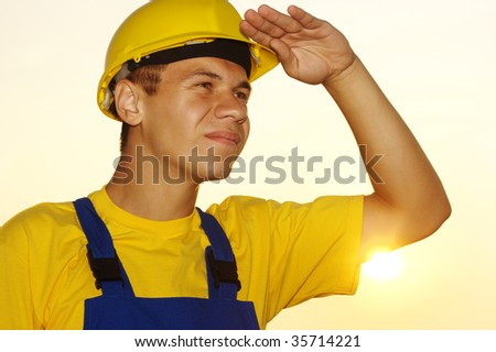 Young worker looking forward, covering eyes from the sun, dressed in blue-and-yellow uniform and hard hat - stock photo