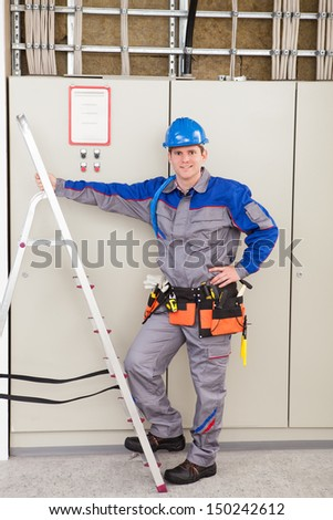 Young Worker Man With Hard Hat Leaning On Ladder - stock photo