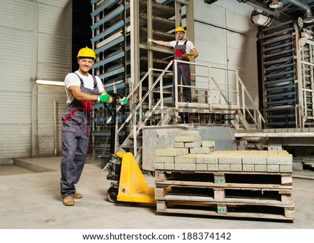 Young worker moving paving stones with pallet truck on a factory - stock photo