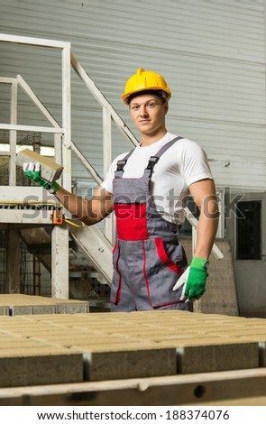 Young worker near conveyor belt with paving stone  on a factory   - stock photo