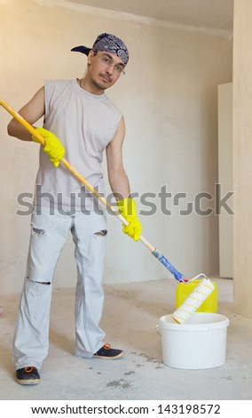Young worker painting ceiling with painting roller. Home improvement - stock photo