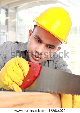 young worker sawing wood