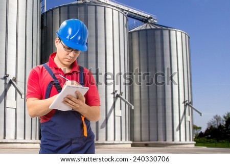 Young worker taking notes in front of silos company - stock photo