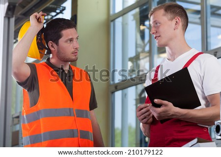 Young worker talking with his manager, horizontal - stock photo