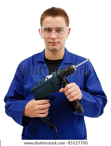 Young worker with goggles holding drilling machine in front of him - stock photo