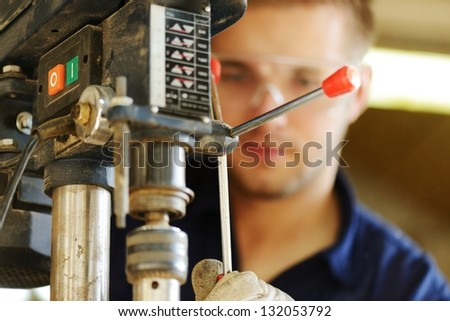 Young worker working in workshop - stock photo
