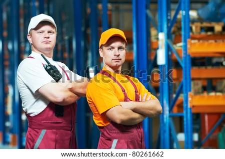 young workers men in uniform in front of warehouse rack arrangement stillages - stock photo