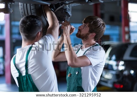 Young workshop employees working together underneath a lifted car - stock photo