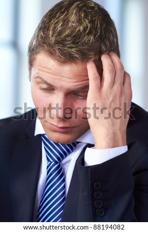 Young worried and stressed businessman scratch his head, very sad face expression - stock photo