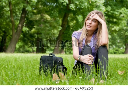 Young worried business woman siting in grass - notebook bag and shoes lying next