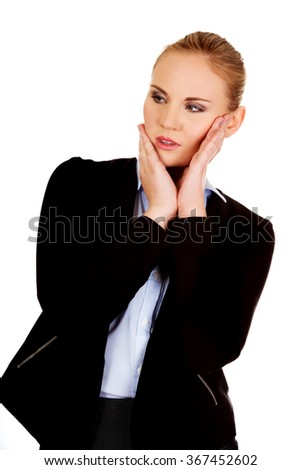 Young worried business woman with hands on cheeks - stock photo