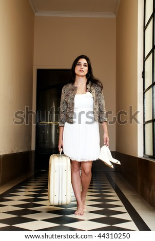 Young worried woman  with an old suitcase - stock photo