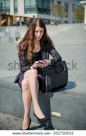 Young worried woman with unhappy expression holding mobile phone - outdoors in urban setting - stock photo
