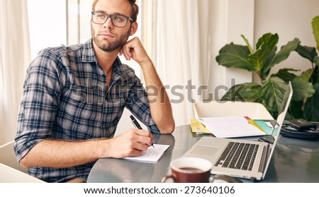 Young writer wearing a check shirt and glasses looking out at the view from his home office's window, taking notes every now and then from his notebook and a black coffee - stock photo