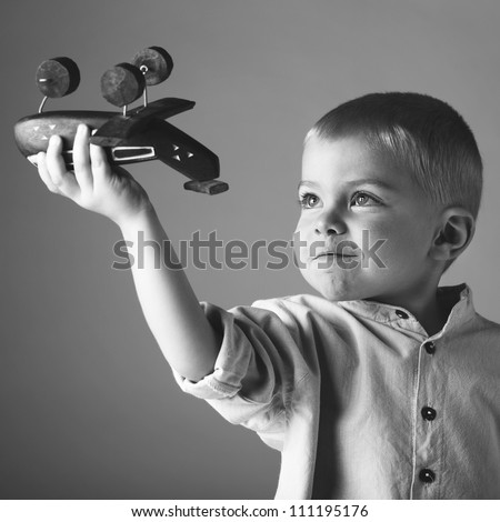 young 3 year old boy wearing long sleeve shirt playing with wooden toy airplane in his hand on studio background in black and white - stock photo