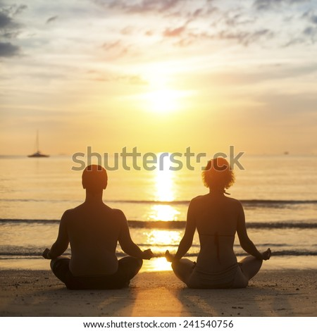 Young yoga couple is meditating in the Lotus position on the sea beach during sunset. - stock photo