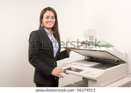 Young young businesswoman making copies on the photocopy machine at the office - stock photo