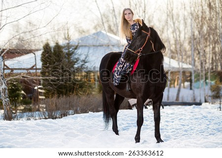 Young young girl goes on a brown horse - stock photo