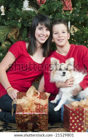 Youngsters sitting by a Christmas tree with presents and holding their pet. - stock photo