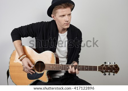 Youong caucasian man in black clothes and hat playing on acustic guitar