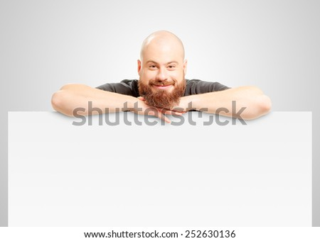 Your advertising below. Happy young man with long beard in casual wear leaning at copy space and smiling while standing against white background - stock photo
