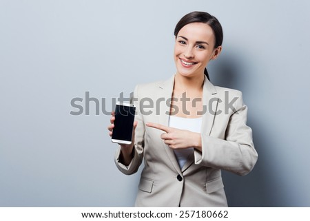 Your advertising on her phone. Beautiful young businesswoman holding mobile phone and pointing on it while standing against grey background - stock photo