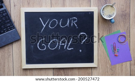 Your goal written on a chalboard at the office - stock photo