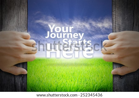 Your Journey Starts Here motivational quotes. Hand opening an old wooden door and found a texts floating over green field and bright blue Sky Sunrise. - stock photo