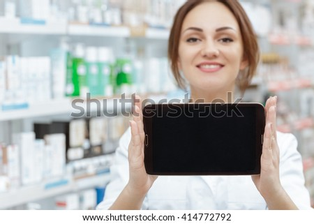 Your order is ready. Selective focus on a digital tablet with the copyspace on in hands of a cheerful pharmacist at the local drugstore.  - stock photo