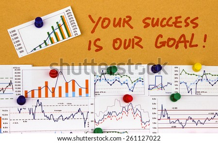 your success is our goal handwritten on paper with financial charts - stock photo