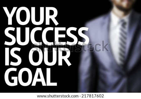 Your Success Is Our Goal written on a board with a business man on background - stock photo