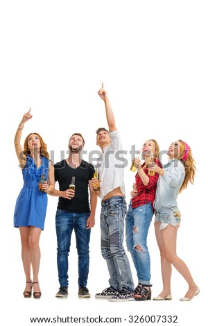 Your tex here. Party and relax. Group of amazed friends with bottles of beer looking up and pointing copy space. Isolated on white. - stock photo