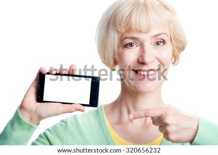 Your text here. Attractive middle aged woman showing screen of smartphone with copy space. Isolated on white. - stock photo