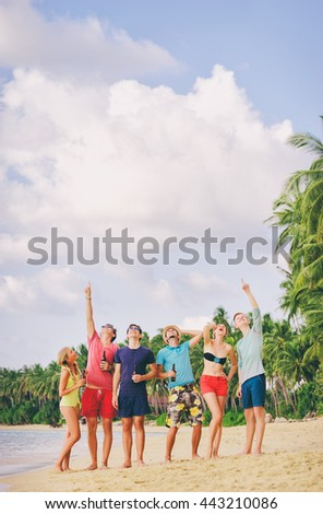 Your text here. Beach party. Group of amazed friends with bottles of beer looking up and pointing copy space. - stock photo