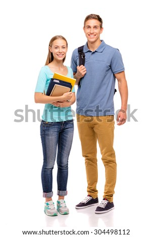 Youth and education. Young attractive students couple standing together. Full length studio portrait. Isolated on white. - stock photo