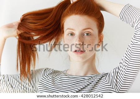 Youth and happiness concept. Close up view of beautiful Caucasian teenage girl in sailor shirt, looking at the camera, playing with her long ginger hair. Young woman with perfect healthy freckled skin - stock photo