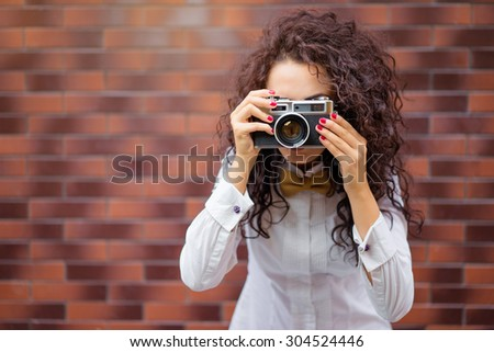 Youth and photography. Young attractive brunette woman holding camera while standing against brick wall. - stock photo