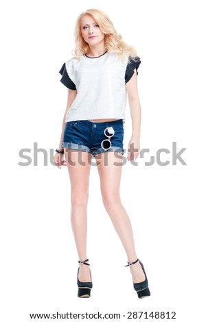 Youth and summer fashion. Gorgeous young woman in shorts and high heels. Isolated on white. - stock photo