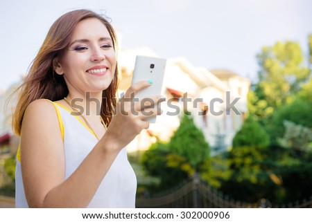 Youth and technology. Attractive young woman using smartphone outdoors. - stock photo