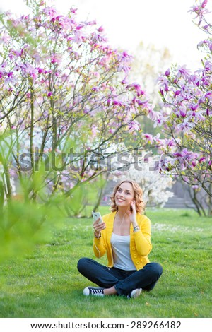 Youth and technology. Listening music. Attractive young woman using smartphone in earphones while sitting on grass in spring park. - stock photo