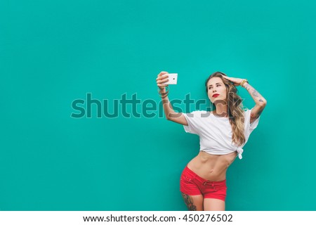 Youth and technology. Pretty sporty young woman in shorts taking selfie on smartphone. Green background.