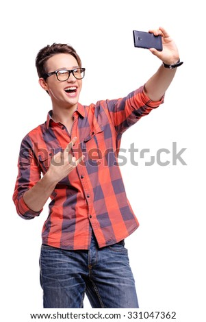Youth and technology. Studio portrait of happy handsome young man taking selfie on his smart phone. Isolated on white, - stock photo